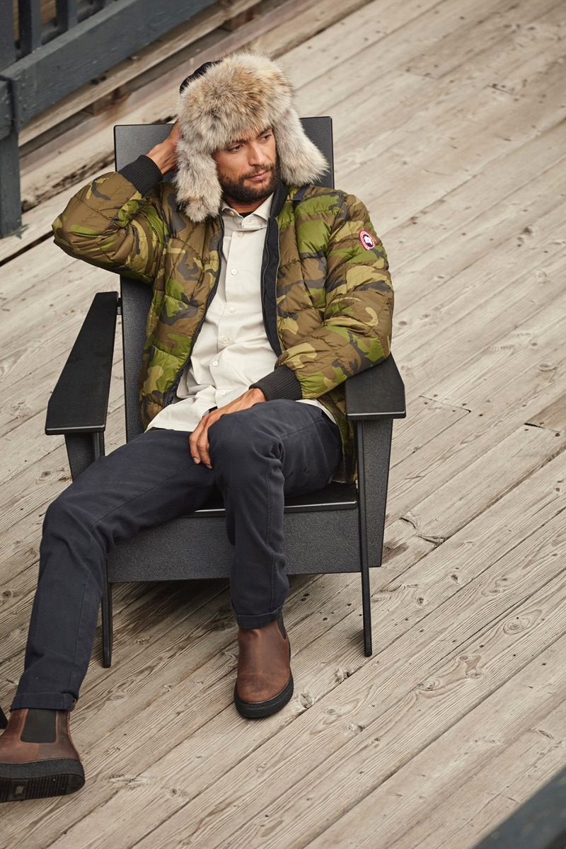 Stealing a moment to relax, Steven sports Canada Goose's Fraser Reversible Bomber Jacket.