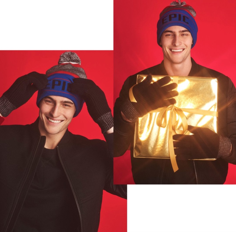 All smiles, Rhys Pickering sports a sweatshirt, bomber, and pom beanie from Express.
