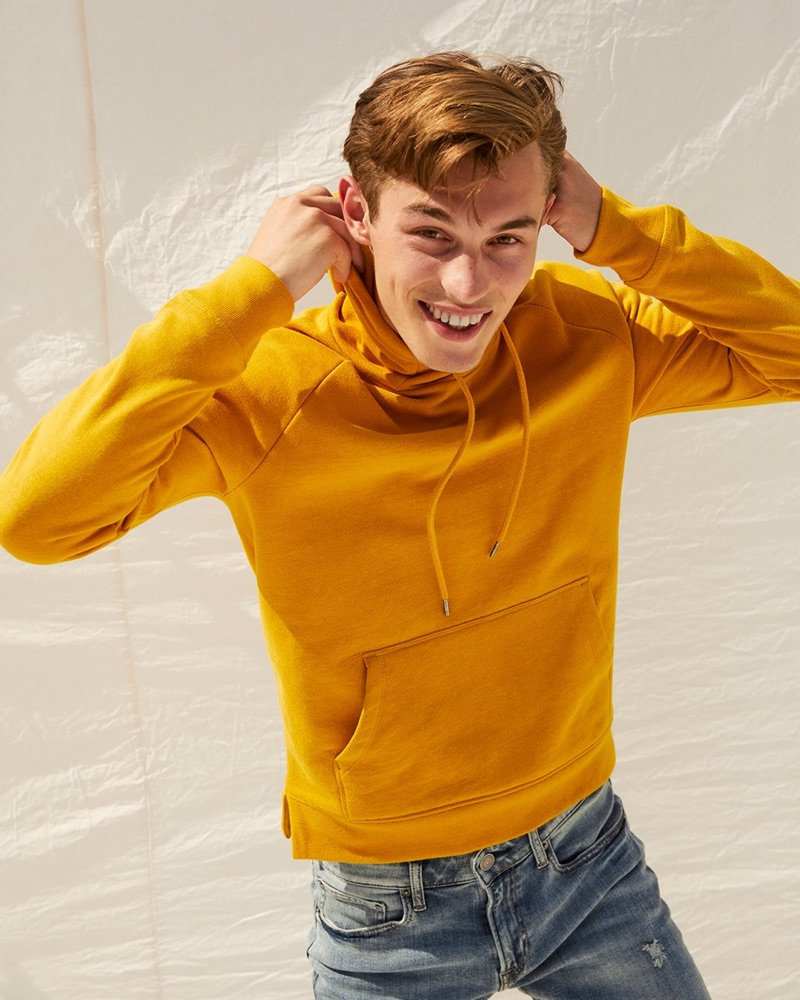 Kit Butler rocks a yellow fleece funnel neck hoodie from Express.