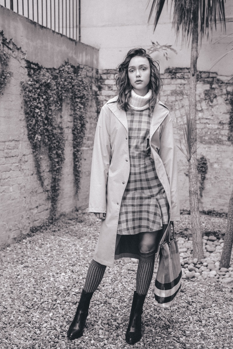 Esme wears raincoat Rains, checked dress Maison Kitsune, sweater Peregrine, bag Burberry, and boots Pregis.