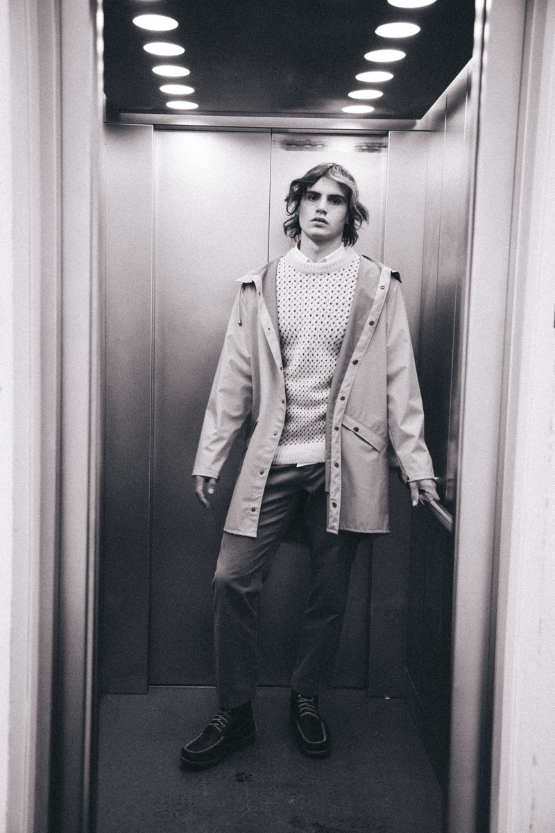 Kit wears raincoat Rains, sweater You Must Create, trousers Norse Projects, shirt Remus Uomo, and boots GH Bass & Co.