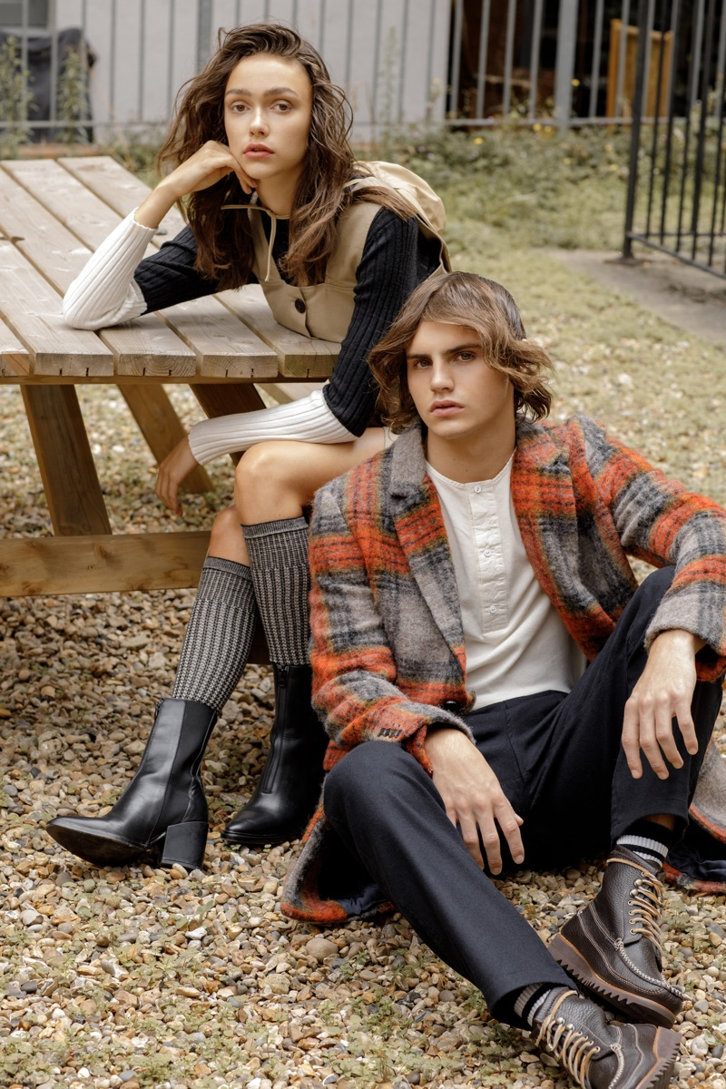 Esme wears sweater and dress Maison Kitsune, boots Peregrine. Kit wears checked coat Scotch & Soda, henley Lee Cooper, trousers You Must Create, and boots GH Bass & Co.