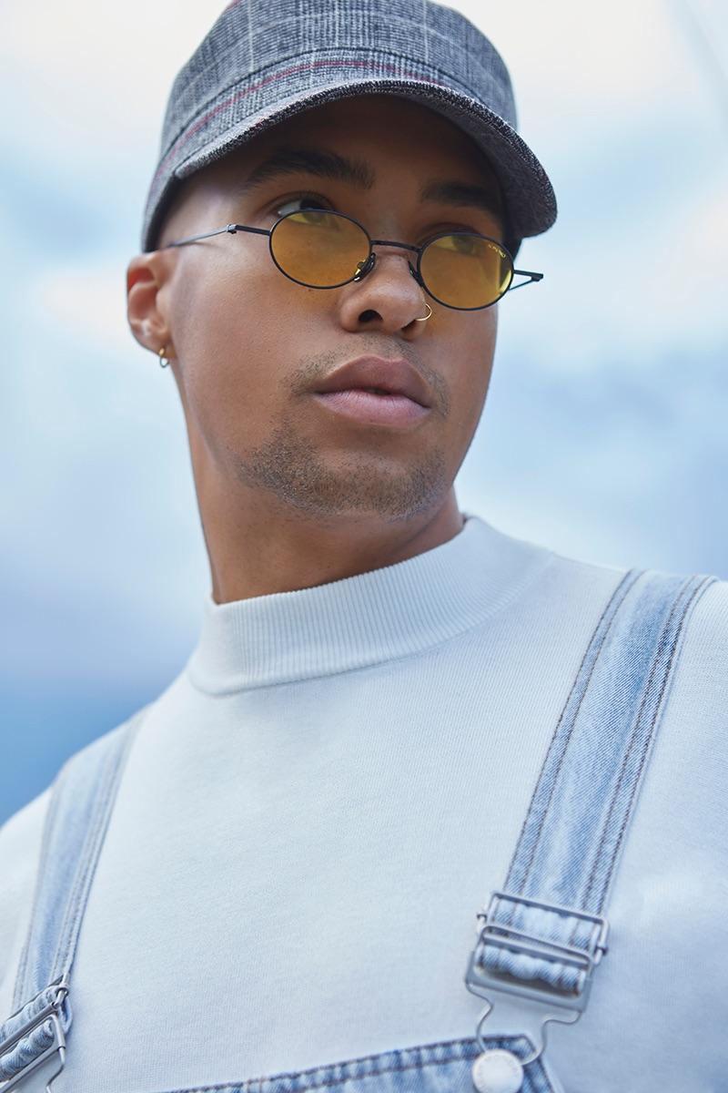 Isak wears shirt Zara, overalls Cheap Monday, hat Reserved, and sunglasses Komono.