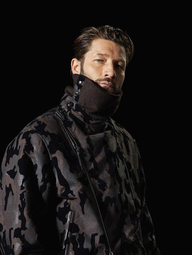 John Halls sports a camouflage print funnel neck jacket from Giorgio Armani.