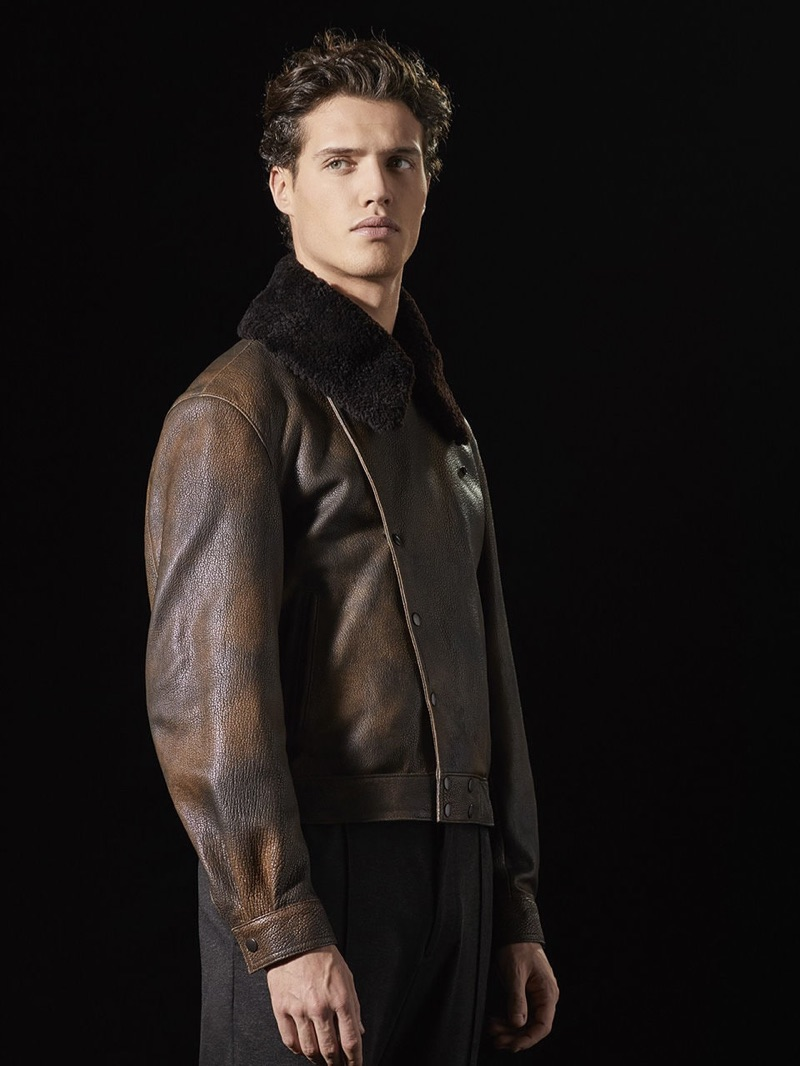 Front and center, Federico Novello sports a brown leather jacket with a shearling collar by Giorgio Armani.