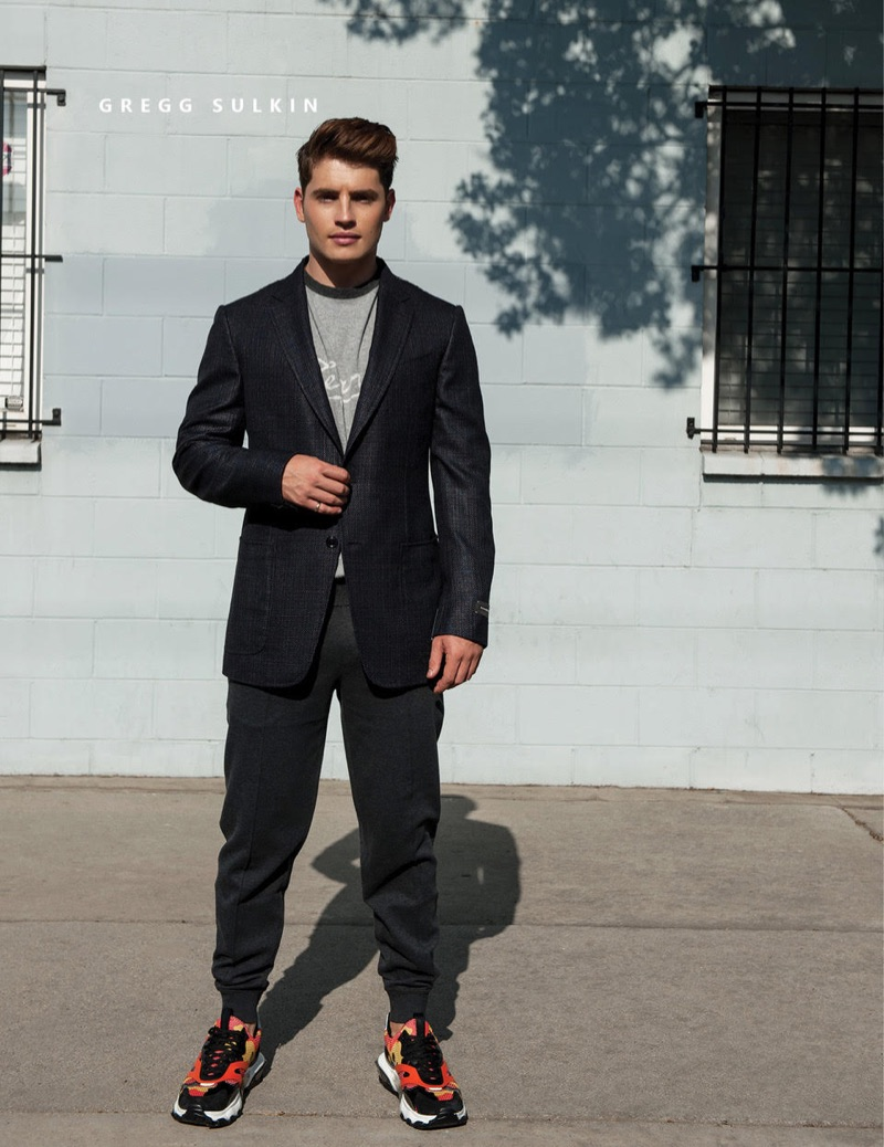 Gregg Sulkin rocks an Ermenegildo Zegna suit jacket and sweater with Brunello Cucinelli pants and Valentino sneakers.