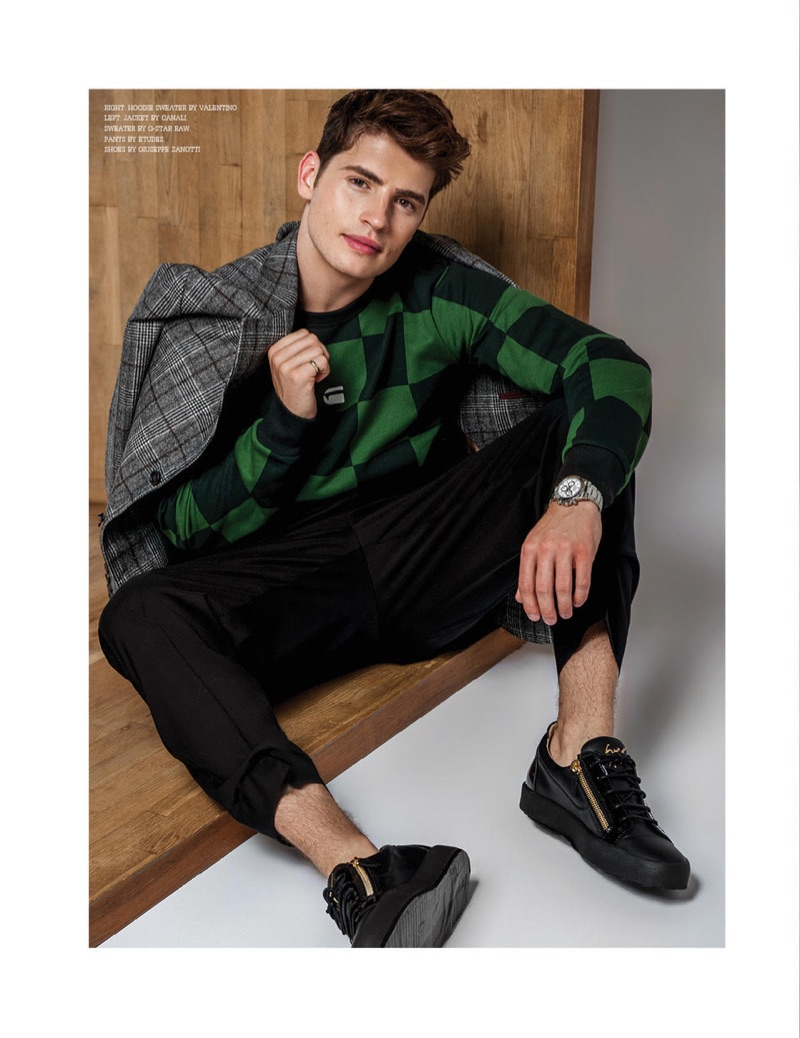 Actor Gregg Sulkin dons a Canali suit jacket, G-Star Raw sweater, Etudes pants, and Giuseppe Zanotti sneakers.