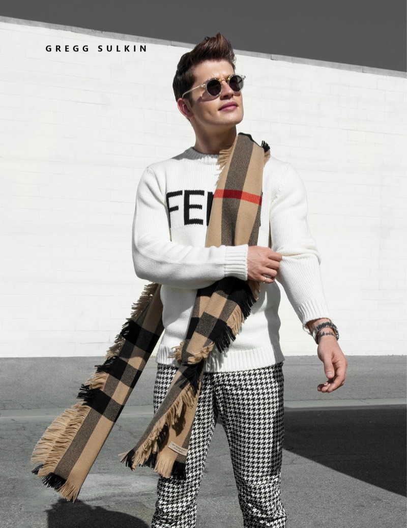 Stepping out, Gregg Sulkin wears a Fendi sweater, Burberry scarf, and G-Star Raw houndstooth pants.