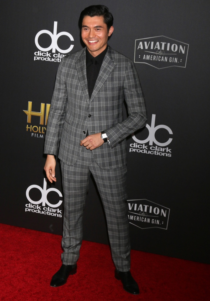 Attending the Hollywood Film Awards, actor Henry Golding looks dapper in a grey check suit by Versace.