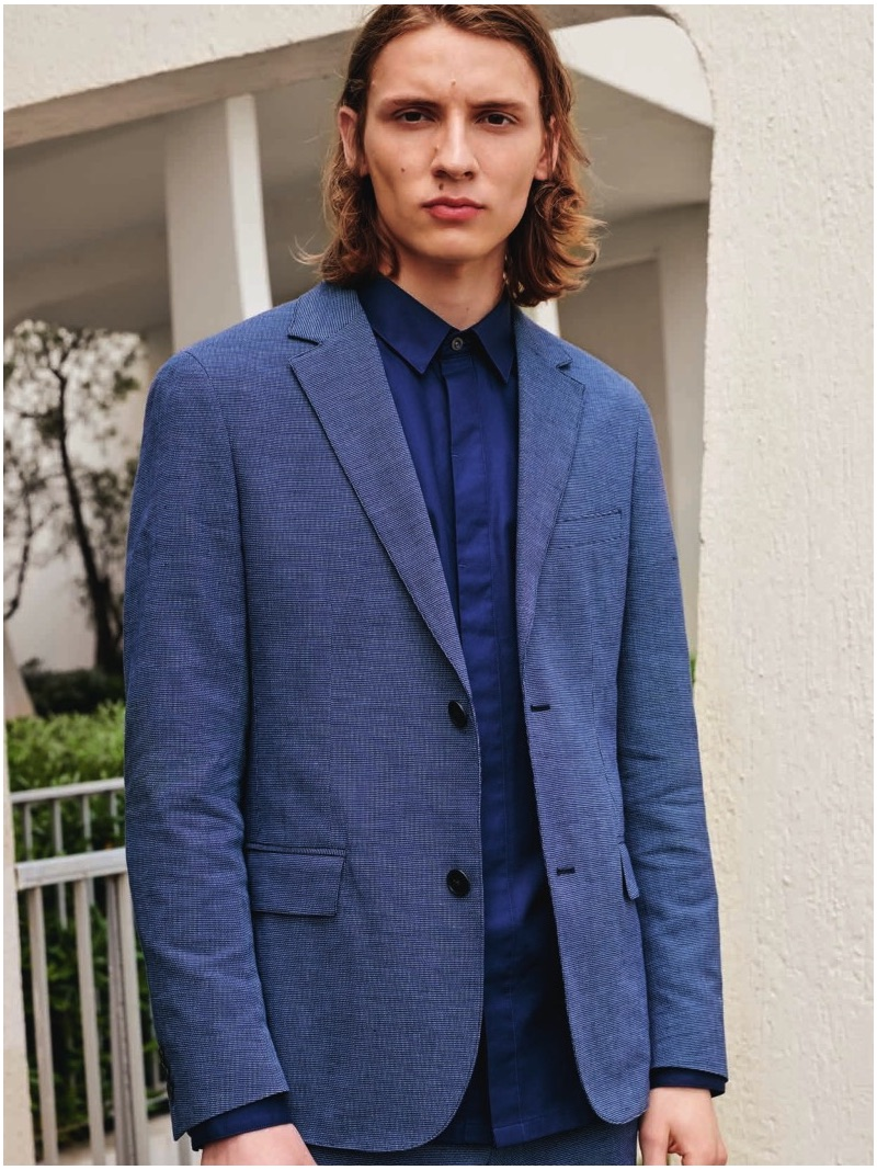 Gabriel Besnard dons a blue suit jacket and shirt from Lacoste's spring-summer 2019 collection.