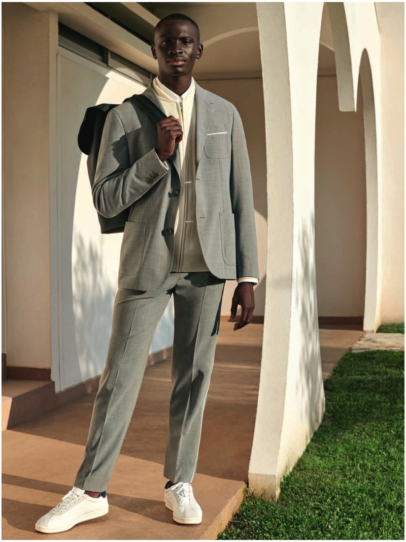A smart vision, Ambroise Mendy wears a suit and white sneakers by Lacoste.