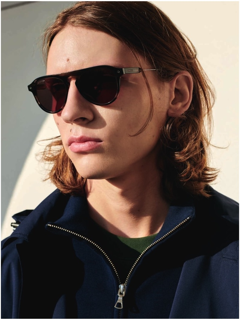 Model Gabriel Besnard sports shades and a pullover by Lacoste.