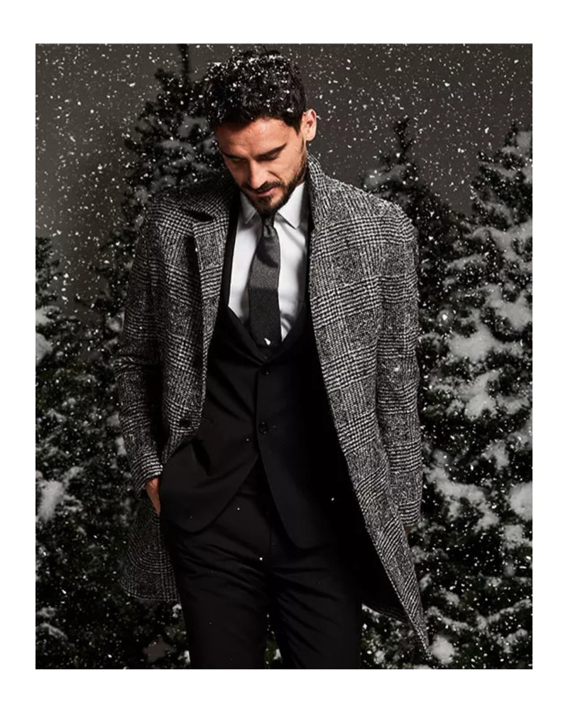Office Holiday Party: Embracing menswear classics, Arthur Kulkov is pictured in a Michael Kors Glen Plaid topcoat with a Calvin Klein black suit jacket and pants.