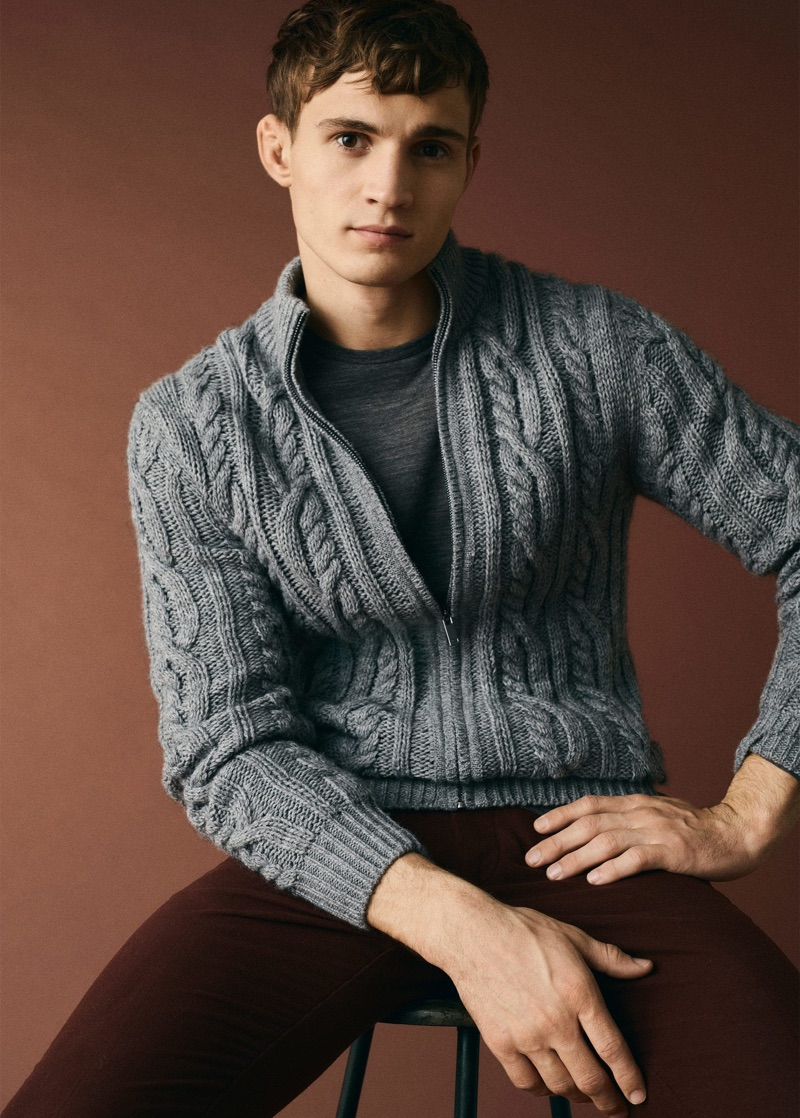 Sitting for a portrait, Julian Schneyder wears a zippered cable-knit sweater from Mango Man.