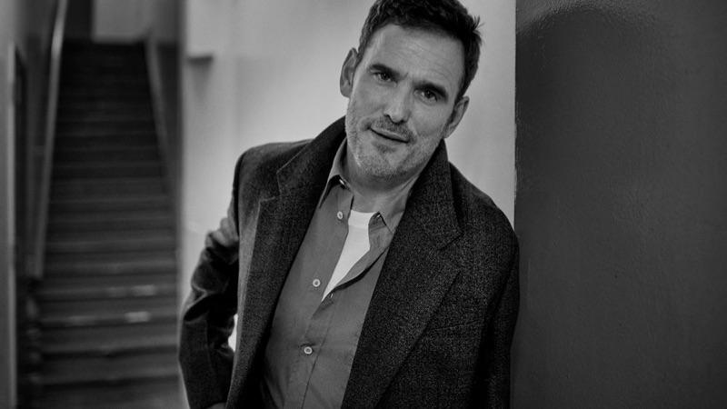 Appearing in a black and white photo, Matt Dillon wears a Prada coat, Maison Margiela shirt, and Berluti t-shirt.