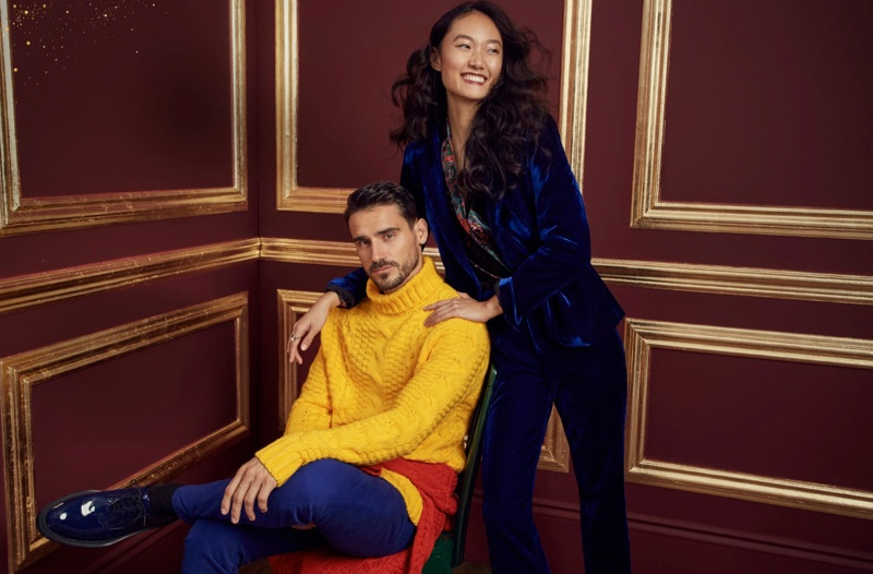 Making a colorful splash, Arthur Kulkov wears a yellow turtleneck sweater and colored jeans from LE 31. In addition to Calvin Klein sapphire blue shoes, Arthur sports another LE 31 sweater tied around his waist.