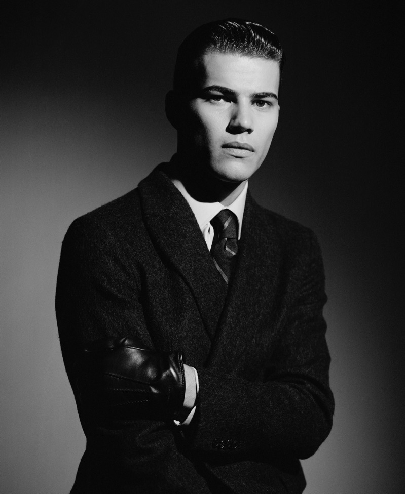 Louie Warner wears a double-breasted coat, shirt, and tie from Giorgio Armani.