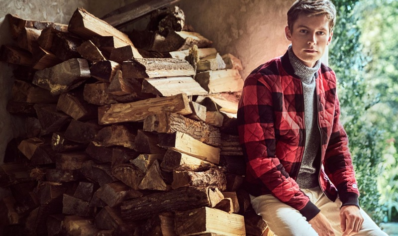 Tapping into rugged style, Janis Ancens rocks a Todd Snyder + Champion red buffalo check quilted bomber with a marled grey chunky cashmere turtleneck sweater.