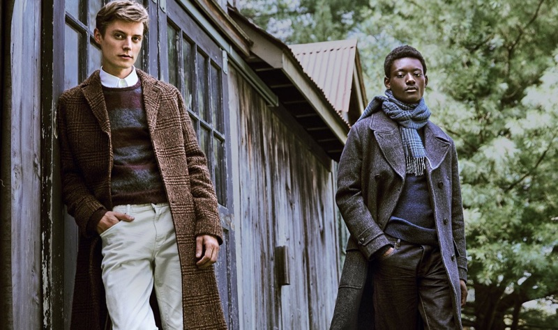 Models Janis Ancens and Youssouf Bamba prepare for the holidays with Todd Snyder. Left to Right: Janis dons an Italian wool bouclé glen plaid topcoat in brown. He also sports an Italian brushed wool rugby striped sweater and 5-pocket stretch pants. Meanwhile, Youssouf models a Todd Snyder Italian wool twill officer coat and navy sweater with a Drake's wool glen check scarf.