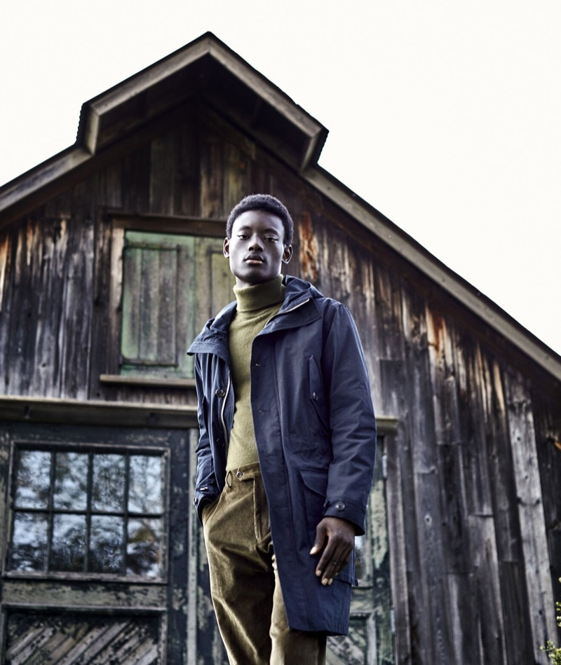 Embracing fall tones, Youssouf Bamba wears a Todd Snyder olive green cashmere turtleneck sweater and green corduroy trousers. A navy Todd Snyder parka completes Youssouf's look.