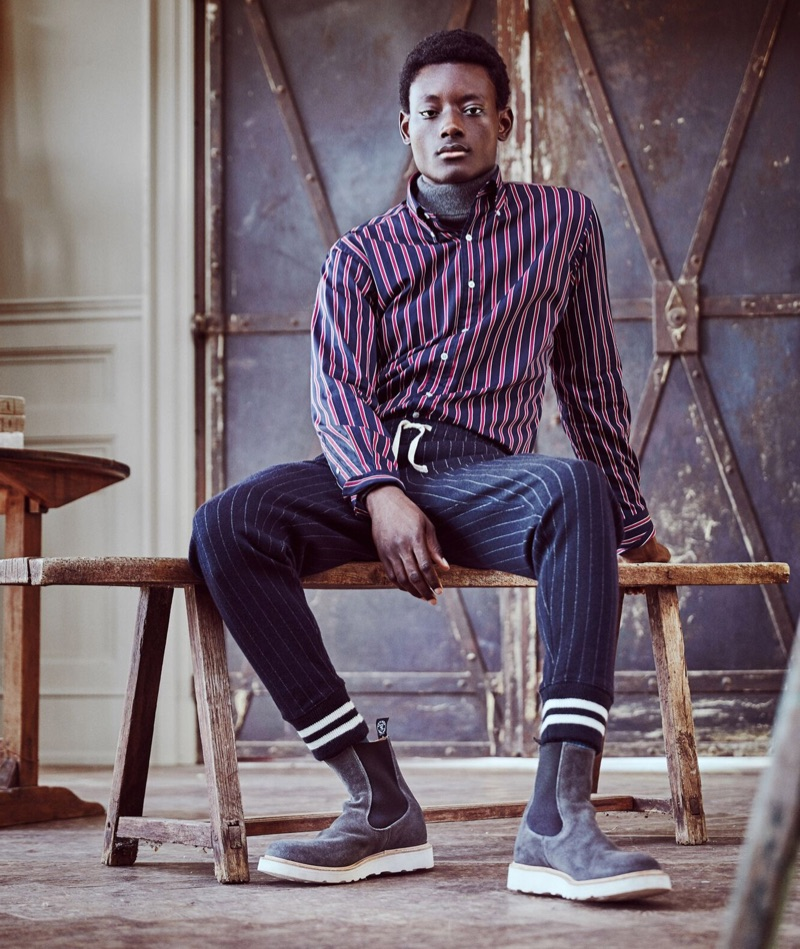 Mixing prints, Youssouf Bamba wears Todd Snyder + Champion wide stripe sweatpants with a Hamilton + Todd Snyder stripe shirt. He also rocks a marled grey chunky cashmere turtleneck and Tricker's Chelsea boots.