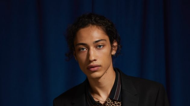 Max Fieschi models an UO black skinny fit blazer and suit pants with a Lacoste leopard print polo.