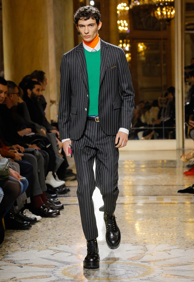 Piero Mendez dons Versace's pinstripe suit during the label's fall-winter 2018 menswear show.