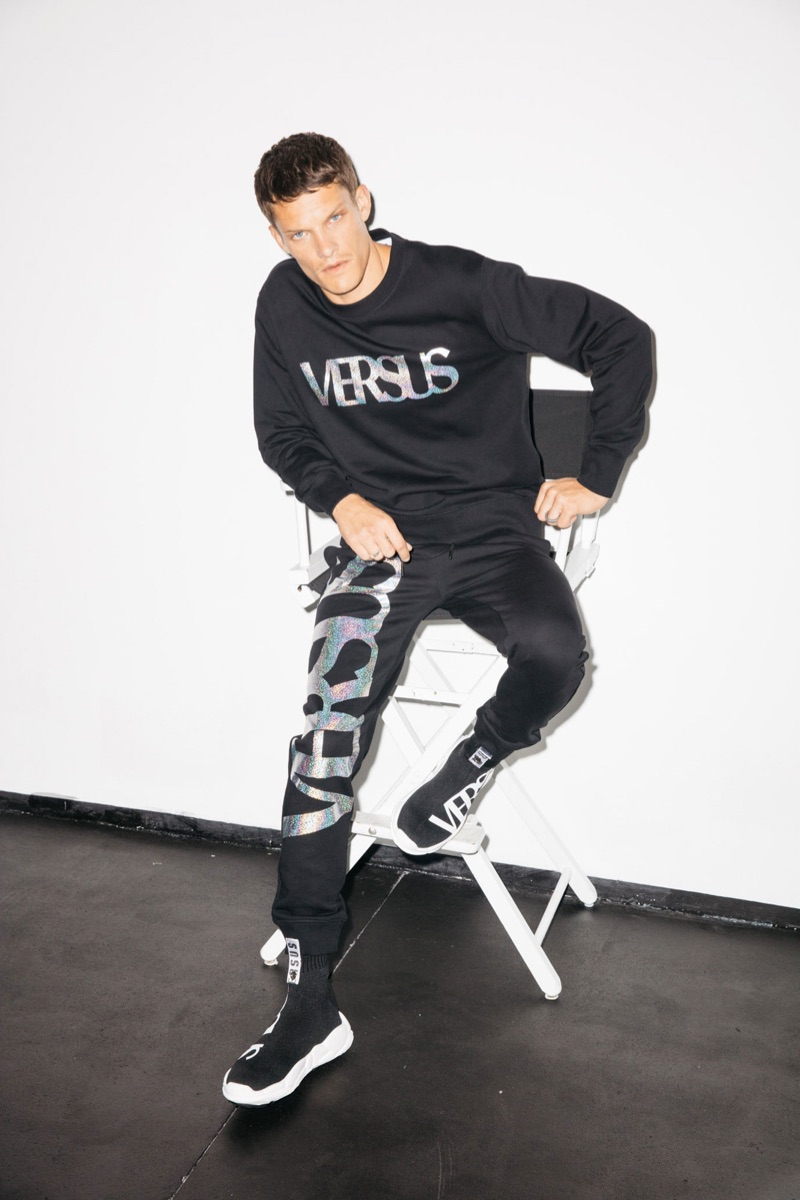 Danny Beauchamp wears a sweatshirt and joggers by Versus Versace.
