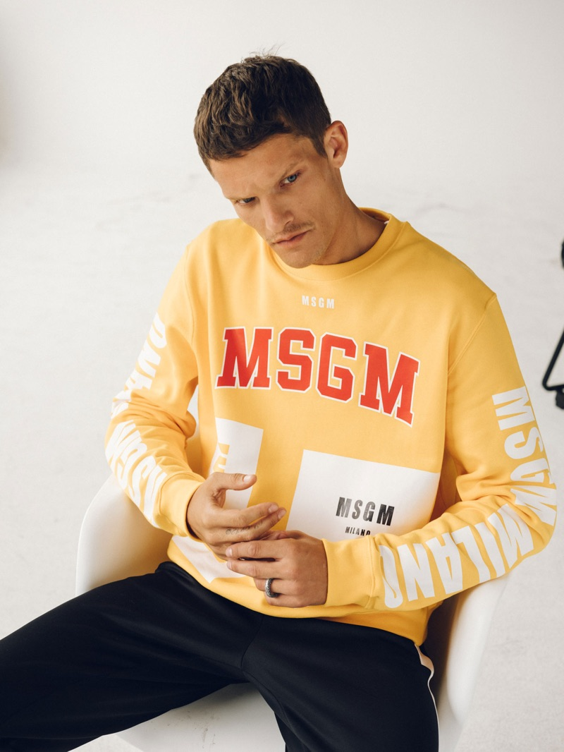 Embracing a pop of color, Danny Beauchamp wears a yellow MSGM sweatshirt.