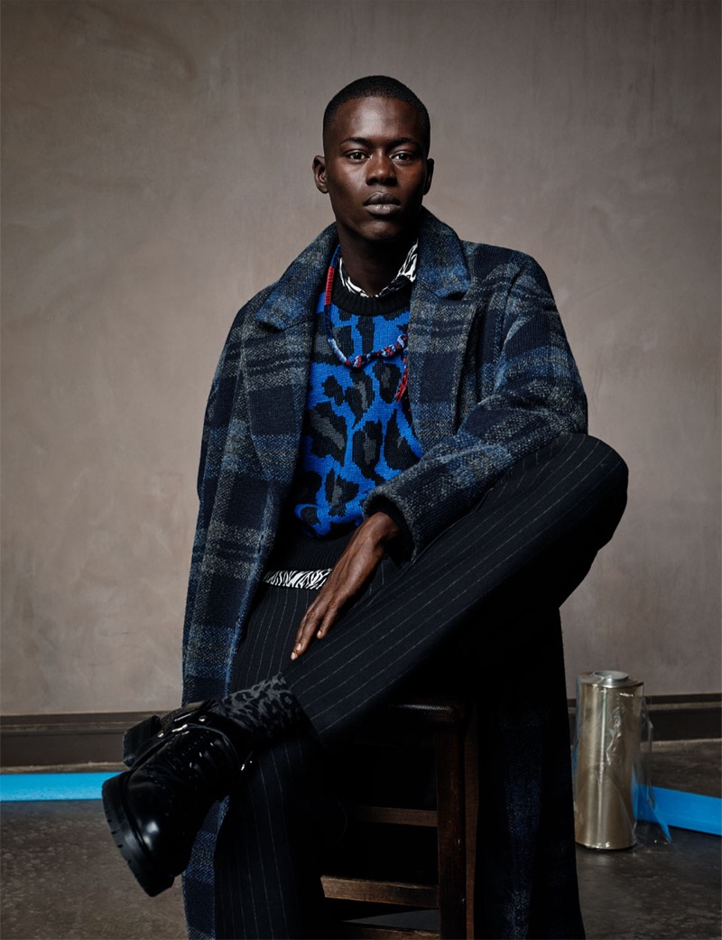 Alpha Dia dons a leopard print sweater with a check coat and pinstripe trousers from Zara Man.