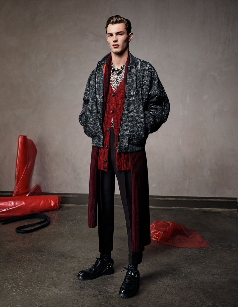Kit Butler sports a houndstooth bomber jacket with a red cable-knit cardigan sweater, slim-fit trousers, and a leopard shirt by Zara Man.