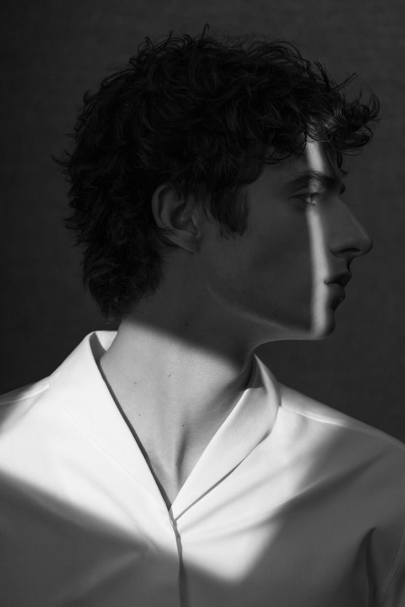 Delivering a side profile, Oscar Kindelan dons a minimal white shirt by COS.