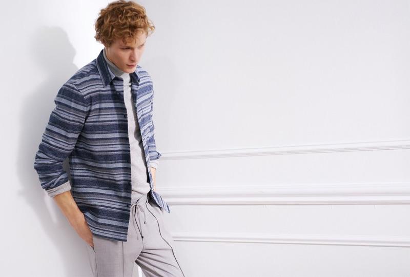 Model Sven de Vries wears a Club Monaco cashmere turtleneck, striped overshirt, and elastic pintuck pants.