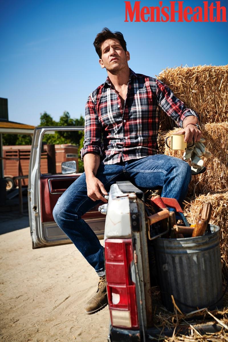 Embracing rugged style, Jon Bernthal wears an Eleventy shirt, Dolce & Gabbana jeans, Allen Edmonds boots, and a Movado watch.