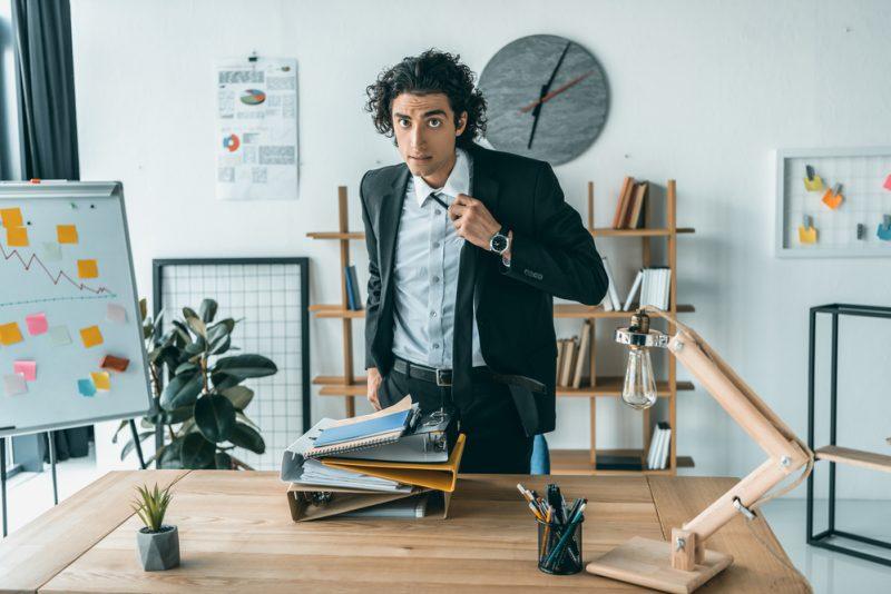 Man Tying Tie in Office