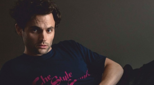 Posing for a studio photo, Penn Badgley wears an Opening Ceremony t-shirt, Bally trousers, and COS shoes.