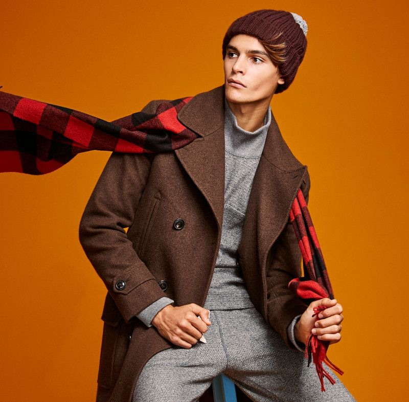 Embracing winter, Parker van Noord dons a brown Todd Snyder Italian yak hair officer coat with a Joshua Ellis red buffalo check cashmere scarf.