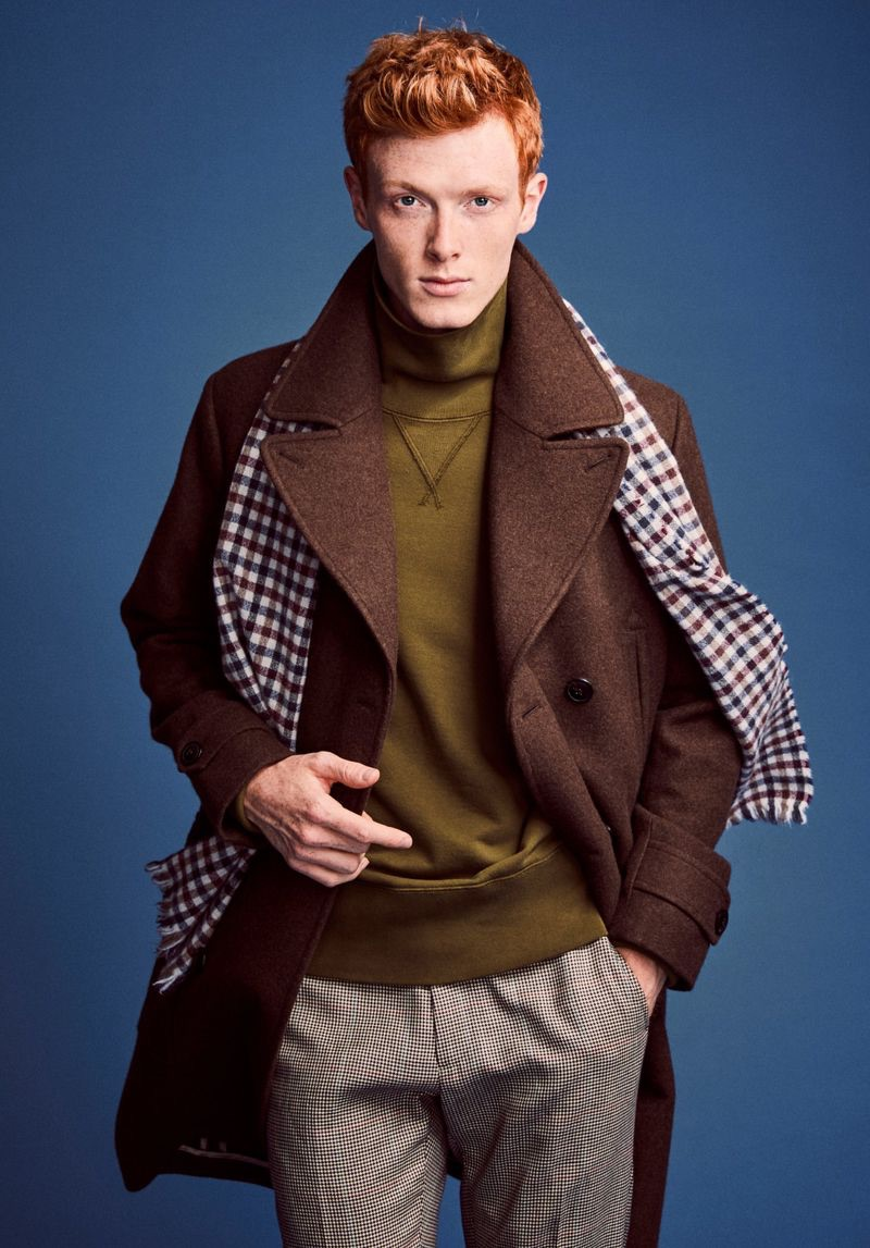 Linus Wordemann dons a Todd Snyder officer coat in brown with Made in New York houndstooth pleated trousers. He also wears a Todd Snyder + Champion turtleneck sweatshirt.