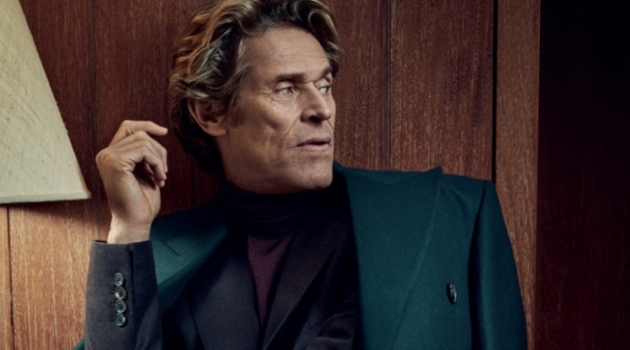 A sleek vision, Willem Dafoe wears a Paul Smith double-breasted coat with a sweater and suit by Gieves & Hawkes.