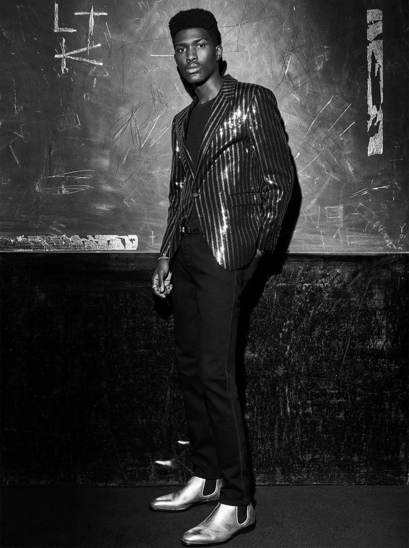 Dressed to impress, Anarcius Jean rocks a metallic striped suit jacket, slim-fit pants, and statement boots by Zara Man.