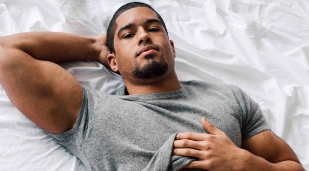 Laying in bed, Anthony Bowens stars in a photo shoot for Gay Times.