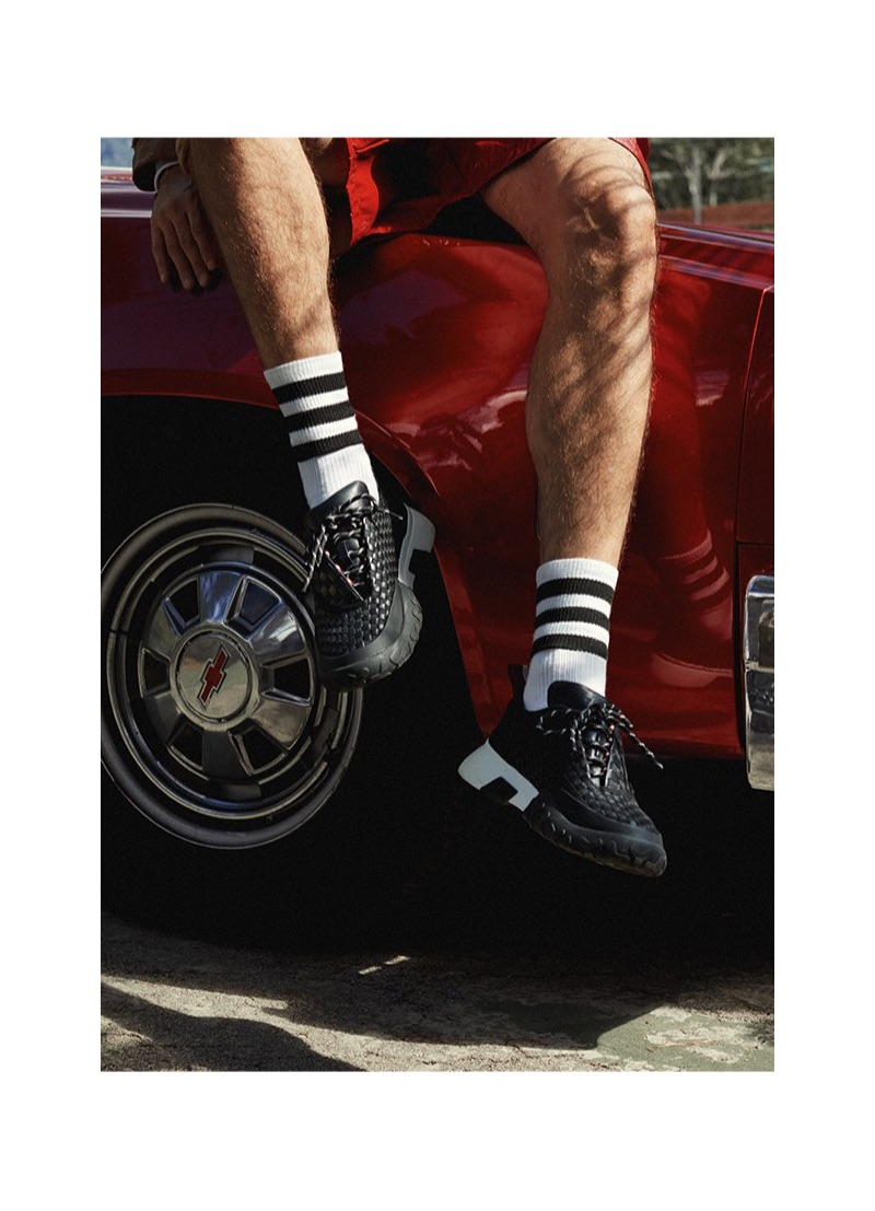 A sporty aesthetic reigns with black sneakers and tube socks from Bally.