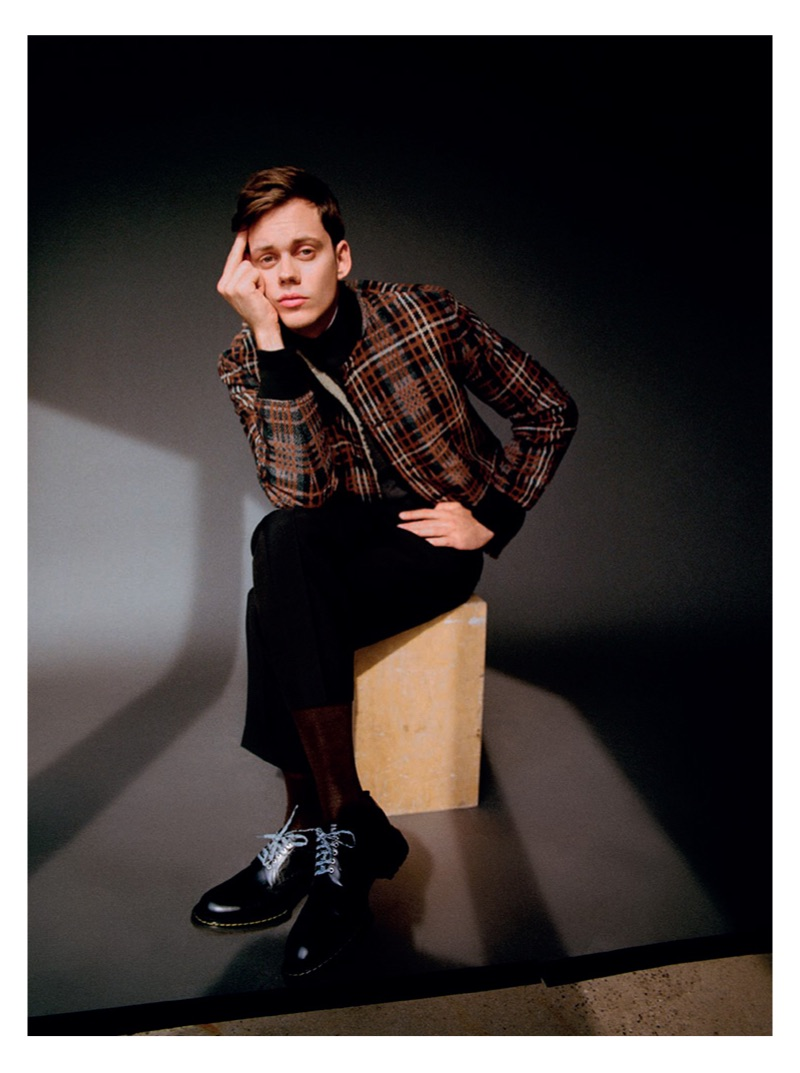Making a graphic statement, Bill Skarsgård sports a checked Cerruti 1881 bomber jacket and pants with a Mango sweater. He also rocks a Dior Men shirt and shoes.