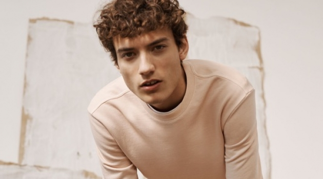 Embracing light hues, Serge Rigvava wears a pink sweatshirt with Connor stretch chinos by Club Monaco.