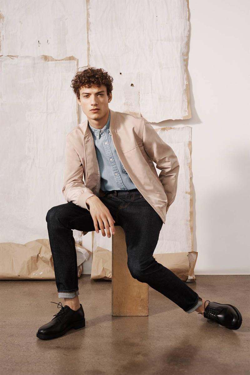 Going smart casual, Serge Rigvava models a Club Monaco bomber jacket, slim denim jeans, an oxford, and Wing + Horns shoes.