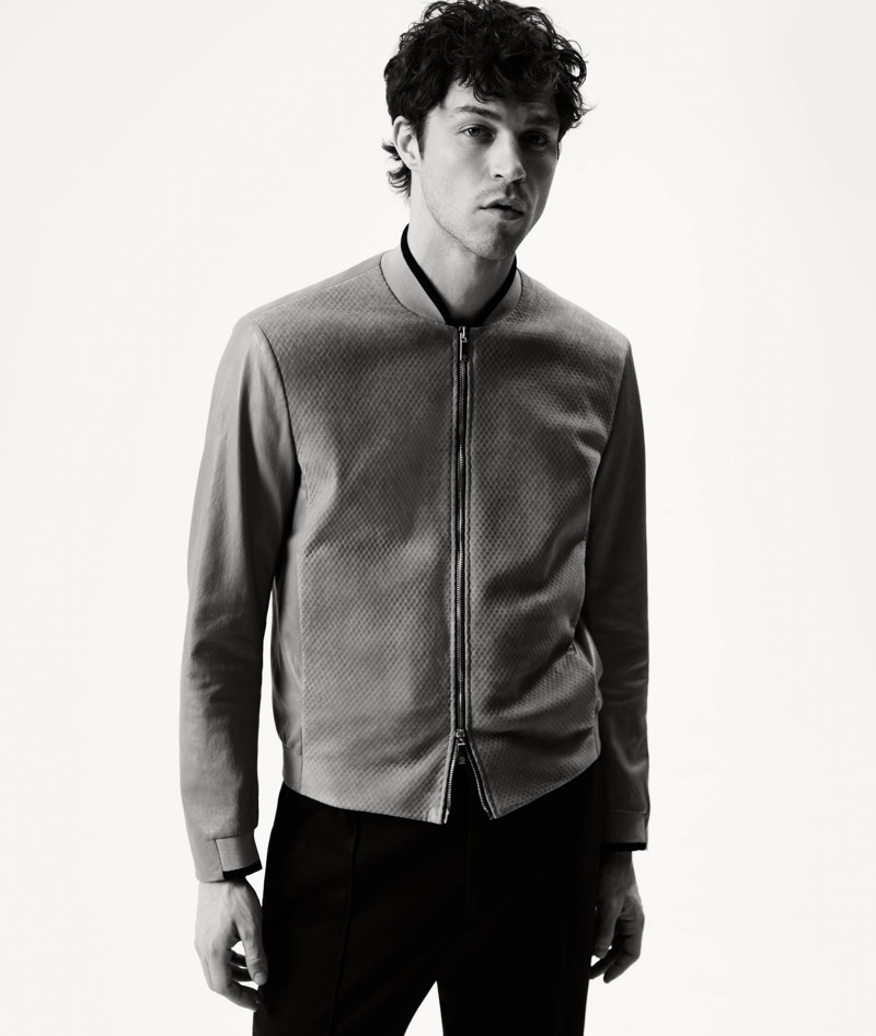 Miles McMillan dons a suede and leather bomber jacket and slim-fit trousers by Giorgio Armani.