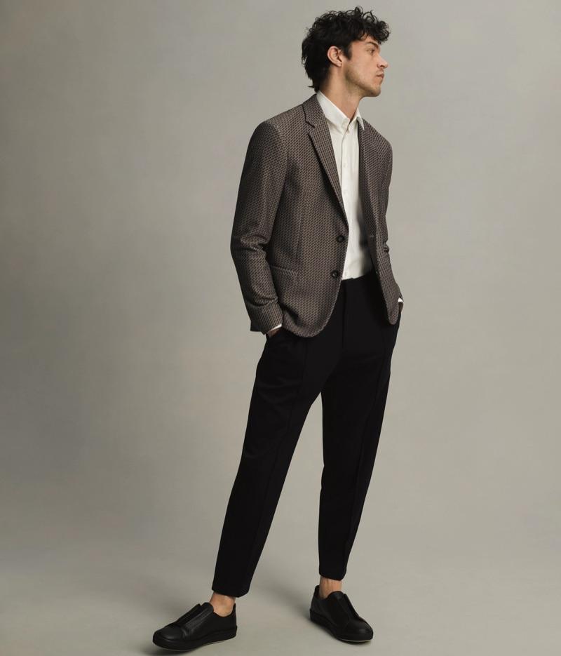 A smart vision, Miles McMillan sports a Giorgio Armani sport coat, dress shirt, and slim trousers.