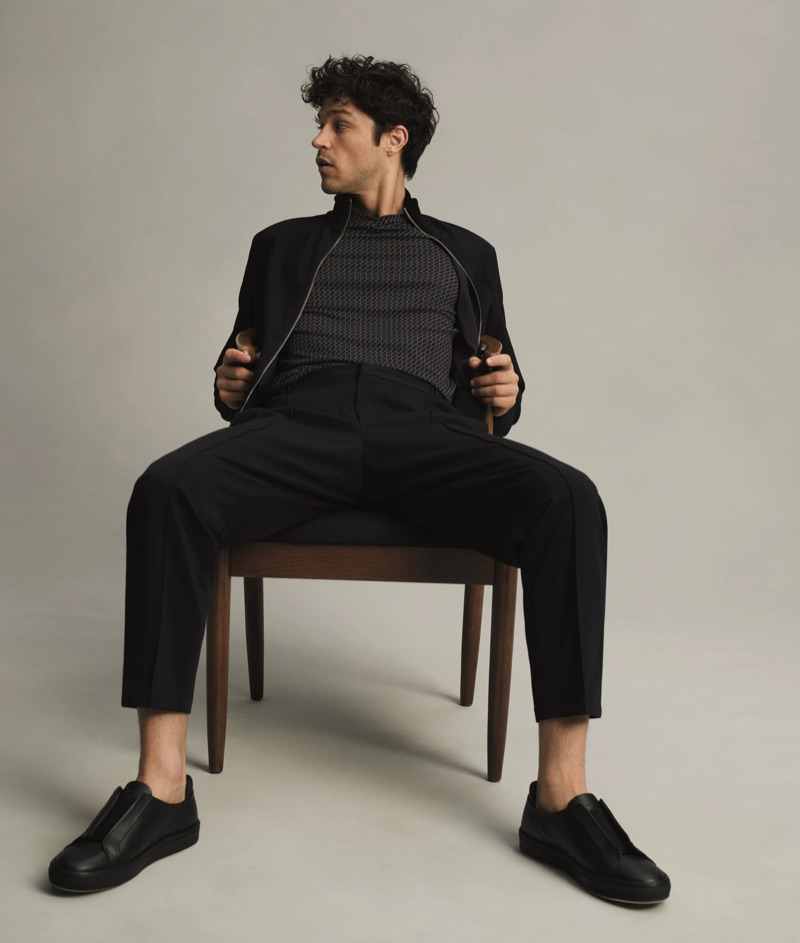 Taking a seat, Miles McMillan sports a Giorgio Armani bomber jacket, jersey t-shirt, and slim trousers.