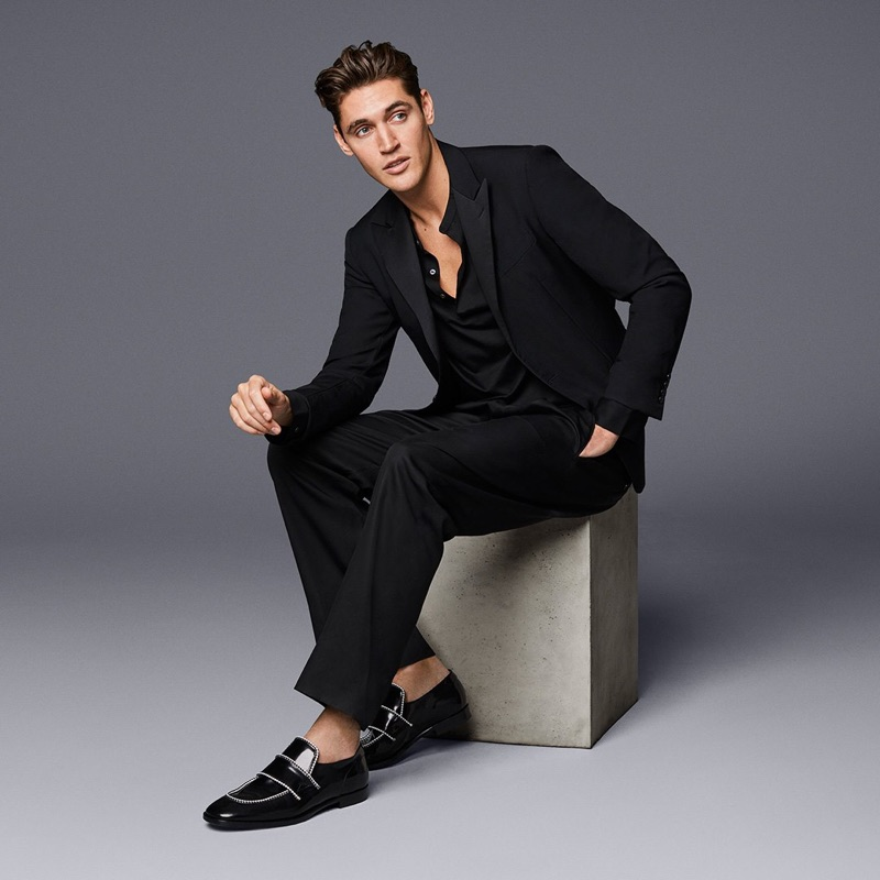 Isaac Carew dons Jimmy Choo's black shiny calf loafers with white rope binding.