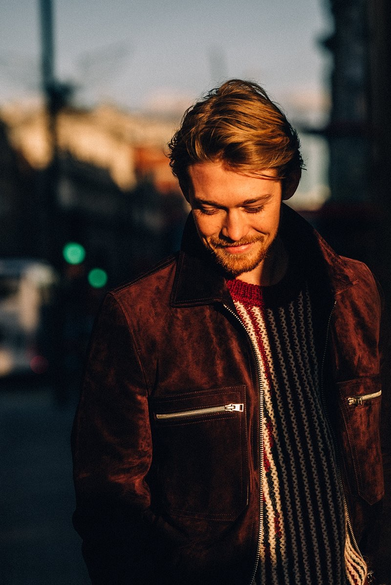 All smiles, Joe Alwyn wears a Tom Ford suede blouson jacket and Saint Laurent striped sweater.